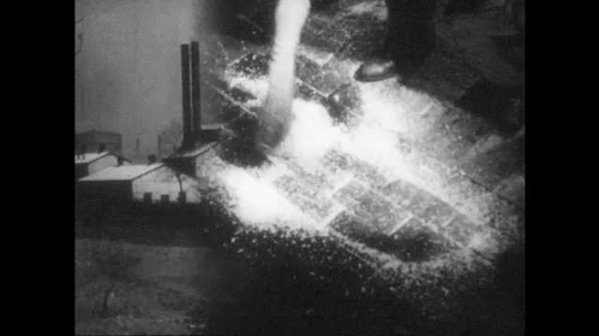 1940s: Man sweeps sawdust around floor. Man stands on ladder, fixes light. Two men talk, man rolls up plans, shakes head. Group of men sit in office, talk.