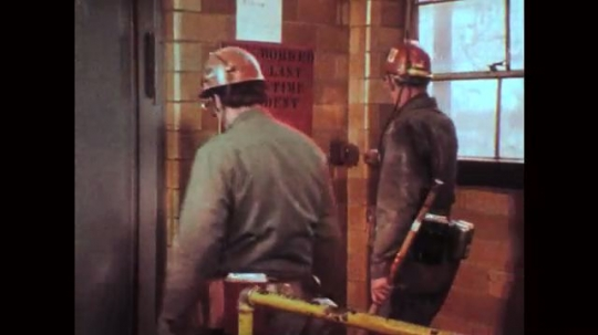 1970s: Man gives lecture with overhead projector. Two mine workers enter elevator. Mine worker inspects and takes notes inside coal mine. Mine worker operates machine and talks to coworker.