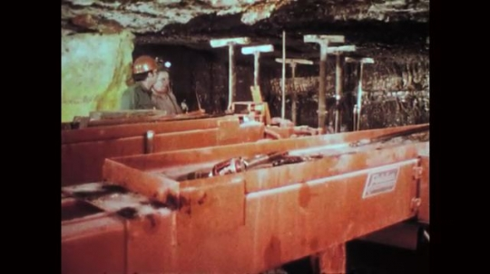 1970s: Two mine workers inside mine stand behind machine, talk. Mine worker stands next to machine, talks. Mine worker operates machine, coworker observes from behind. Conveyor belt transports coals.