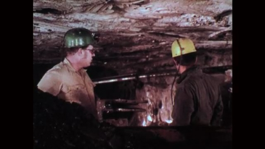 1970s: Mine workers stand next to coal container and talk. Mine worker inspects pipes and talks to his coworker.