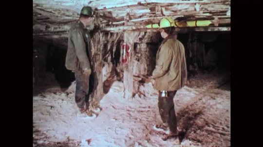 1970s: Mine worker talks to coworker and points to pipes.