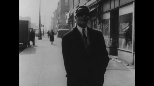 1950s: Man with a blindfold on walks down the street with a cane for the blind. Man swings cane to identify obstacles. Man takes off blindfold.