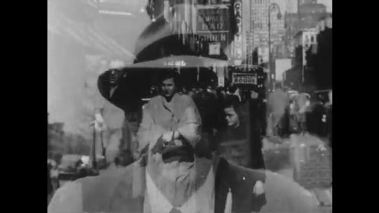 1950s: Man walks down sidewalk next to another man. Cane tip taps on sidewalk, gets stuck in crack.