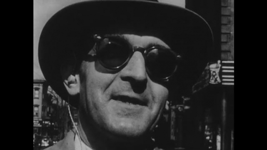 1950s: Blind man stands on city sidewalk, holds cane. Man smiles.
