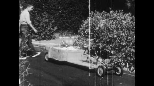 1950s: Boys approach and examine wooden go-cart. Boy sits on go-cart. Hand pulls brake handle, Wooden brake pushes against wheel. Feet stand on pavement. Boy pushes friend in go-cart.