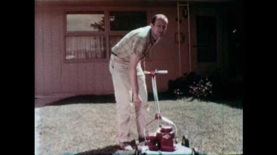 1960s: Man puts hand on hip and looks at mower. Man mowing lawn, man pulls mower toward him. Man looks up, sighs, and places hands on hips and shrugs. Shoe appears in man