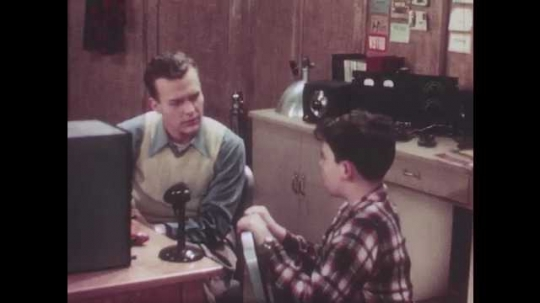 1940s: Boy talks with man in an amateur radio studio, man gives ocarina to boy, boy blows into ocarina. Oscilloscope graphic moves in different shapes.