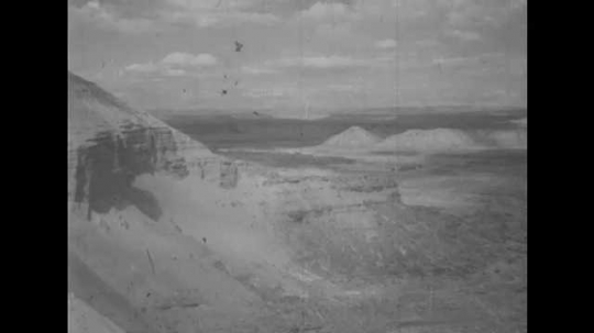 1950s: UNITED STATES: view cross Utah landscape. Wild and rugged desert basin. Man and boy look across valley