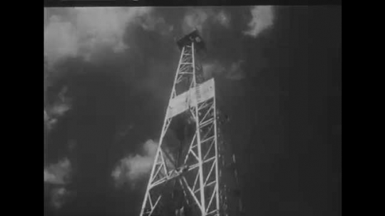 1950s: UNITED STATES: worker on drilling rig. Man and boy arrive at oil well in desert. Man on crane. View inside drilling rig.