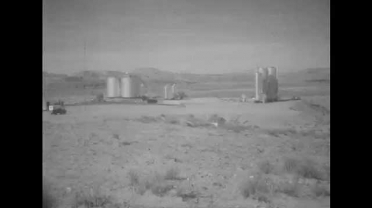 1950s: UNITED STATES: Oil field in Utah desert. Nodding donkey works at oil refinery. Oil and gas towers in desert.
