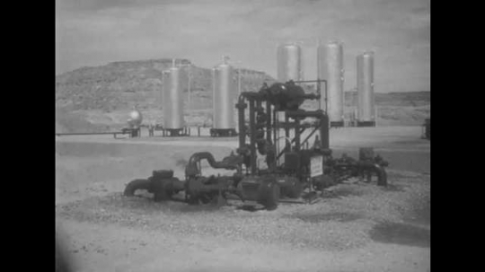 1950s: UNITED STATES: oil refinery and well in Utah desert. Boy and man visit oil plant. Boy visits dog house in desert.
