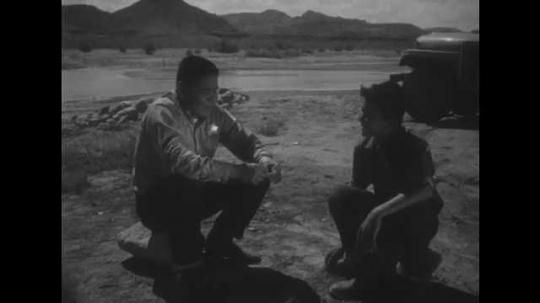 1950s: UNITED STATES: man and boy sit by camp fire. Window Rock sign. Arizona desert. Window rock formation in Arizona desert.