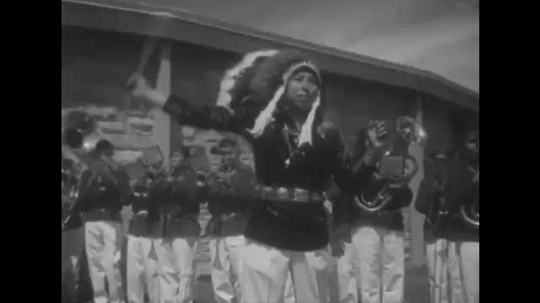 1950s: UNITED STATES: marching band and majorettes at Navajo fair. Civic centre at Window rock. View across exhibit hall