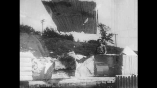 1950s: men pushes large block of limestone or granite on rope from crane onto platform at rock quarry. man in hard hat waves hand for direction.