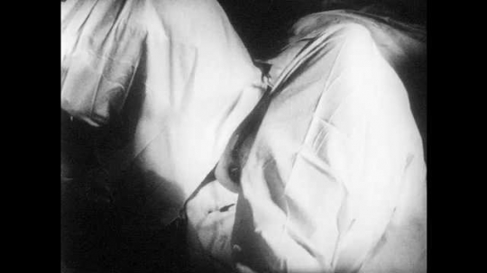 1950s: UNITED STATES: nurse drapes sheets and leggings around lady during child birth. Doctor examines lady during birth