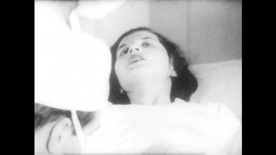1950s: UNITED STATES: lady pants during child birth. Doctor holds swab around vaginal opening. Head emerges from vagina
