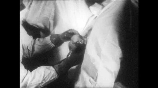 1950s: UNITED STATES: baby appears from birth canal. Shoulders delivered during child birth. Medic holds head of baby during birth