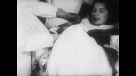 1950s: UNITED STATES: lady holds new baby. Doctor ties umbilical cord. Doctor cuts umbilical cord