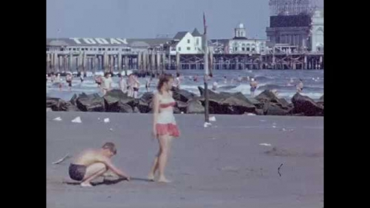 1940s: Boy plays with sand, girl draws line in sand with foot. Woman and man run, look up, waves break in background. Woman walks and holds her dress. Two women walk along beach, people in water.