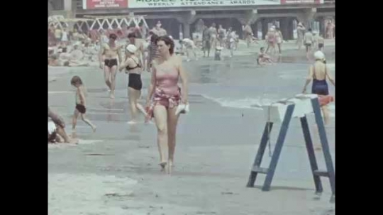 1940s: Woman in swimsuit walks along busy beach. Woman in swimsuit sits in sand. Woman and man sit in the sand. Two women adjust their caps and walk on the beach, kids play with water in background.
