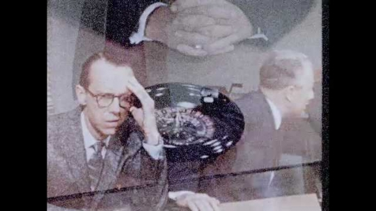 1950s: Man sits at desk, spins small roulette wheel, talks.