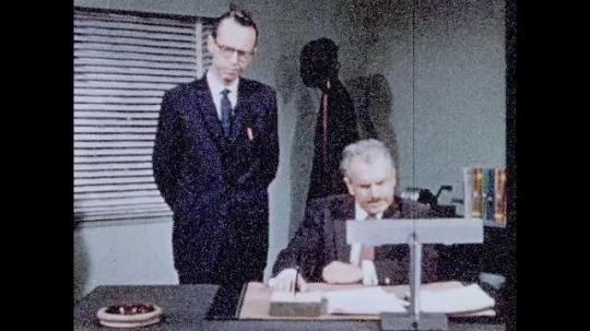 1950s: Men in office talk. Man at desk hands man paper, man reads paper, man drops paper on desk, folds arms, looks upset.