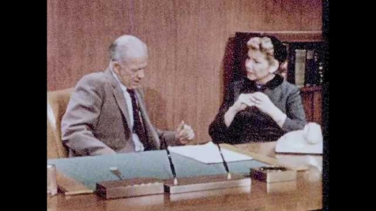 1950s: Woman sits at desk, talks with man sitting behind desk.