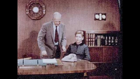 1950s: Woman sits at desk, man stands next to desk, picks up telephone, talks, hangs up phone, pats woman on shoulder. Two men walk into office, smile, nod.