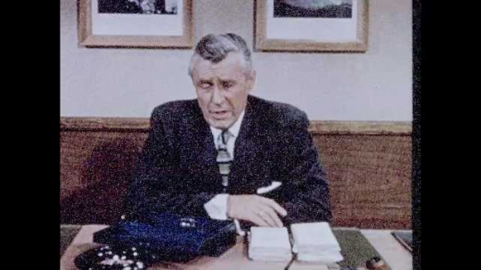 1950s: Man sits behind desk, talks, puts papers into metal box, puts box into drawer, closes drawer, puts key into pocket.