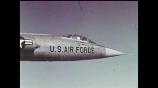 1970s: Lockheed F-104 Starfighter USAF supersonic jet airplane flies through and above thick clouds and rolls over.