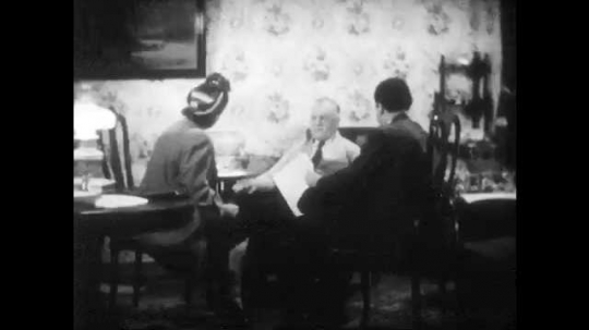 1940s: Farmer sits in parlor with man and woman official. They show him map of proposed airport using his land. Farmer crumples up map and throws it on the ground, shouting.