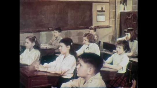 1950s: Children sit and recite together.  Girl.  Boy. Teacher points at chalkboard.