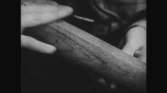 1950s: Hand rubs wood, boys talk. Wall full of mounted tools