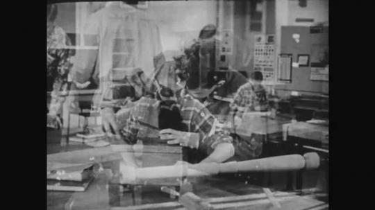 1950s: Boy works with equipment. Boy in class. Man speaks to boy. Boy speaks. Boy chisels wood.