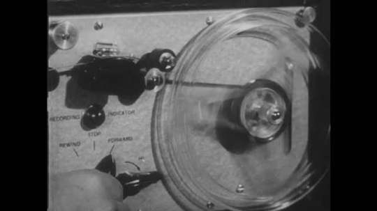 1950s: Hand adjusts recording equipment from