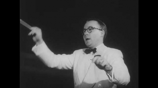1950s: Man in dinner jacket and bow tie waves baton and gestures with his left hand. Choir sings.