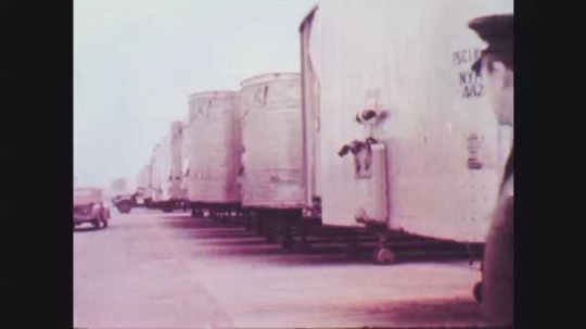 1950s: Man in uniform looks at parked trailers. Truck marked Norwalk Truck Lines drives through parked tractor trailers in yard. Man in uniform walks behind Norwalk truck.