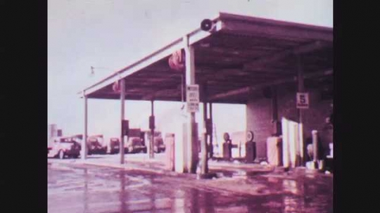 1950s: Tractor trailer pulls into filling station. Attendant crosses in front of track as it pulls in, waves to driver, and approaches pump.