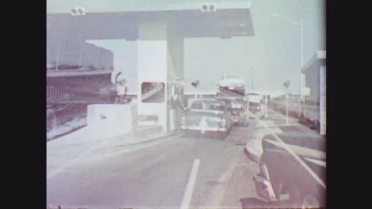 1950s: Car in toll booth fades to POV traveling past snow-covered fields looking at two lanes of a four-lane highway separated by median. POV snowy landscape alongside highway.