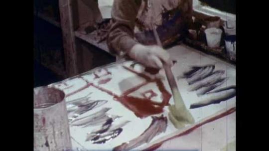 1960s: UNITED STATES: child paints picture on paper. Small boy draws with crayon. Boys draw picture.
