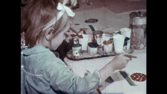 1960s: UNITED STATES: child paints picture at table. Child paints lines on paper. Girl cuts paper with scissors