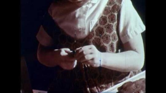 1960s: UNITED STATES: child shapes plasticine. Girls make models. Girl eats pretend lollipop