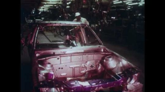 1980s: Views of workers, machines welding in factory. Car engine, pan to man working. Rear view out of moving car. Zoom out on field. Men at blackboard. Man at computer. Men look at papers.