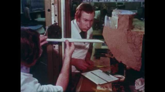 1980s: Men sculpting car part out of clay. Man sculpting. Tracking shot, man working in lab. Hands hold controller. Man looking at model. Close up of machine part moving.