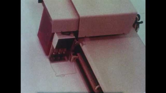 1980s: Computer prints drawing on paper. Close up of machine part, zoom out. Person crouching in wind tunnel, zoom out. Hand presses button, zoom in. Zoom out on wind tunnel. View of gauge.