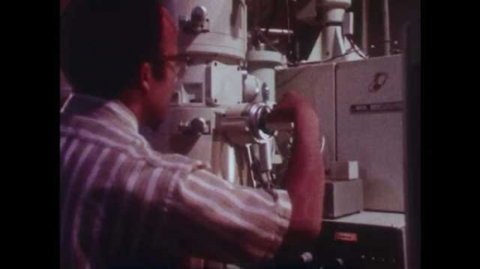 1980s: Man looks into microscope. Magnified view of plastic. Close ups of machine parts moving.