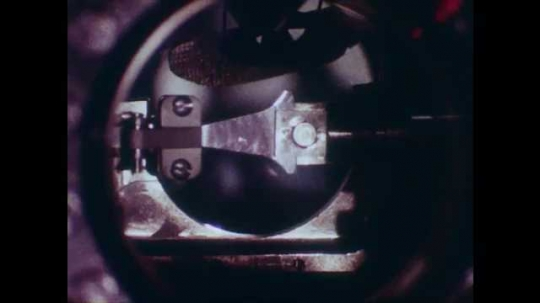 1980s: Close up of metal piece in machine, zoom out to man working with machine, other man enters.