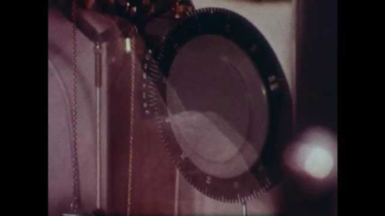1980s: Close up of lab equipment, zoom out to man working. Hand drops material in text tube. Man inserts glass tube into machine.