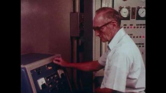 1980s: Man in lab looks through window. High angle shot, men next to engine. Men with equipment in lab. Hand adjusts knob. Laser runs through screen. Man looks at laser. Men in lab.