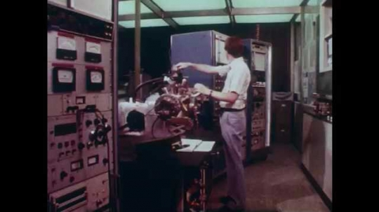 1980s: Man in lab, adjusts spectrometer. Electrical readout prints on graph. Close up, tweezers pick up microprocessor.